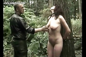 Milf slave tied to a tree gets spanked on her legs and hold-up on her pussy by dextrous
